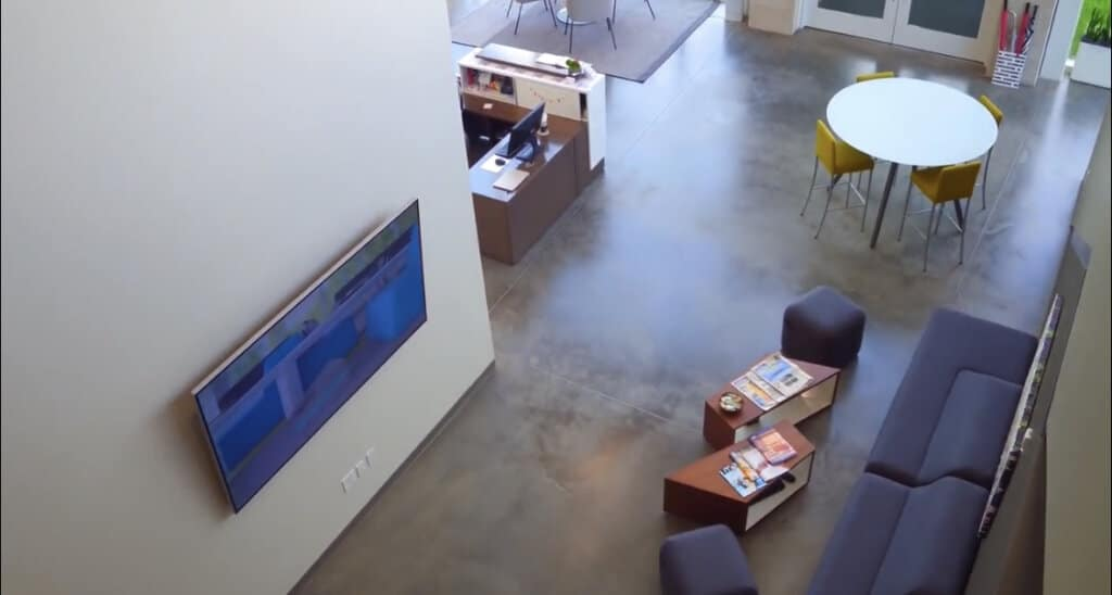 Looking down at a modern, open office space with a waiting area and receptionist desk